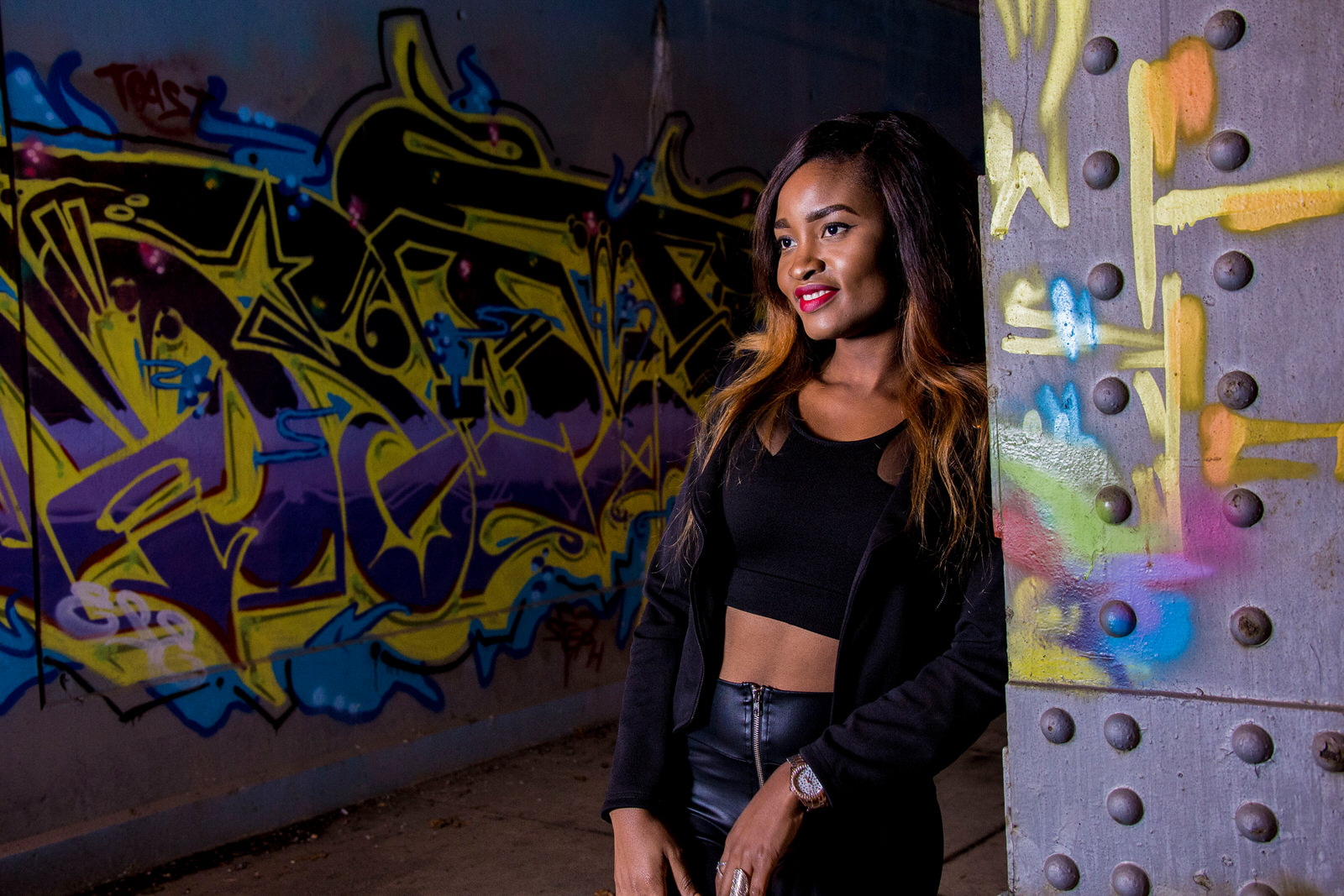 Young woman stands against graffiti railing for senior portraits in Erie, PA