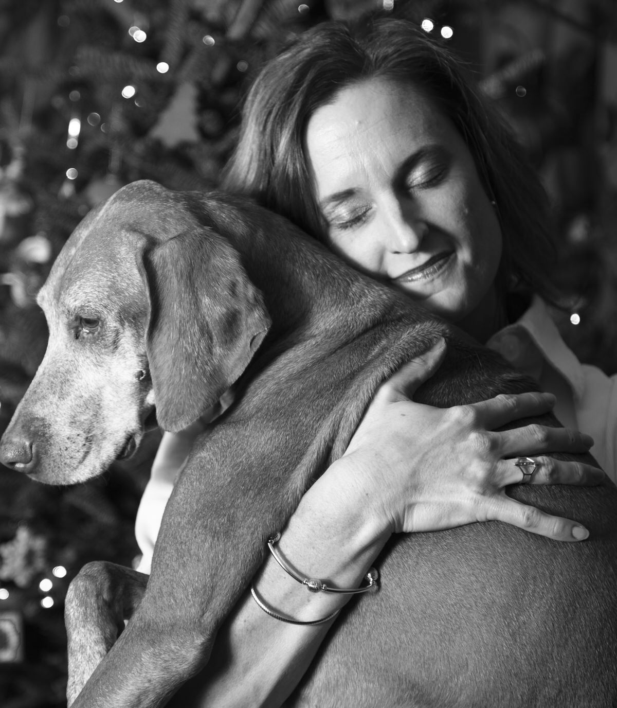 Woman hugs her dog for family portraits