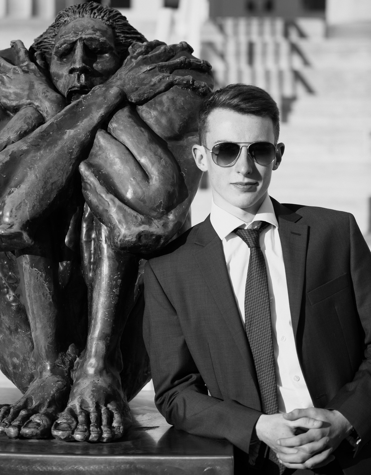 Boy in suit and sunglasses leans against statue for senior portraits in Erie, PA