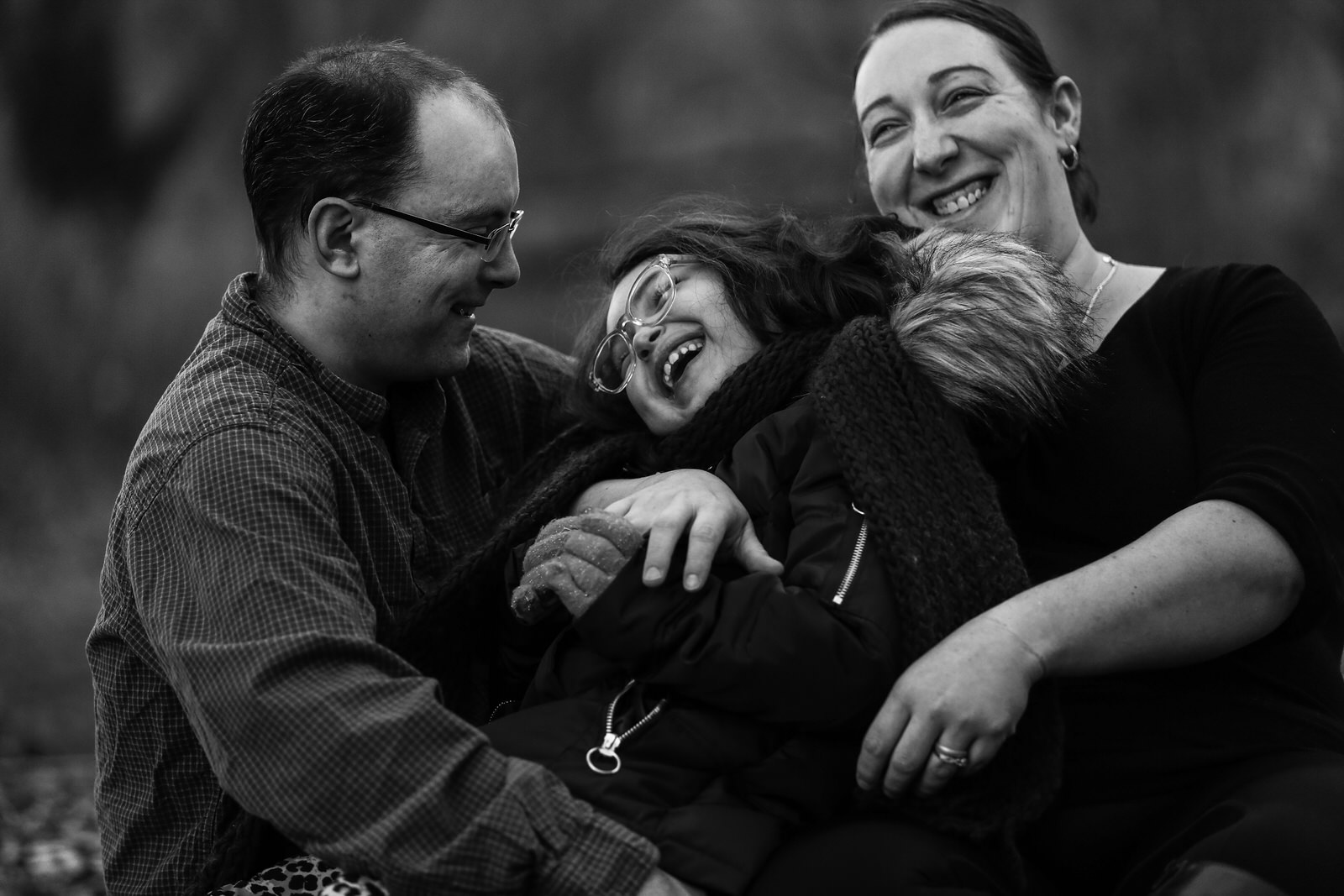 Father, daughter, and mother laughing together during family portraits in Frontier Park In Erie, PA