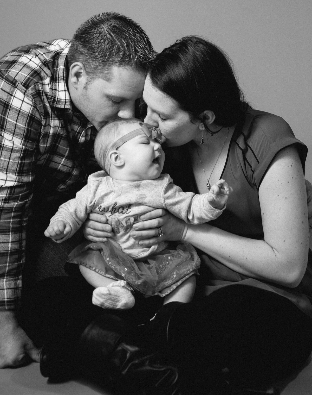 Father and mother kiss the top of baby's head for family portraits in Erie, PA