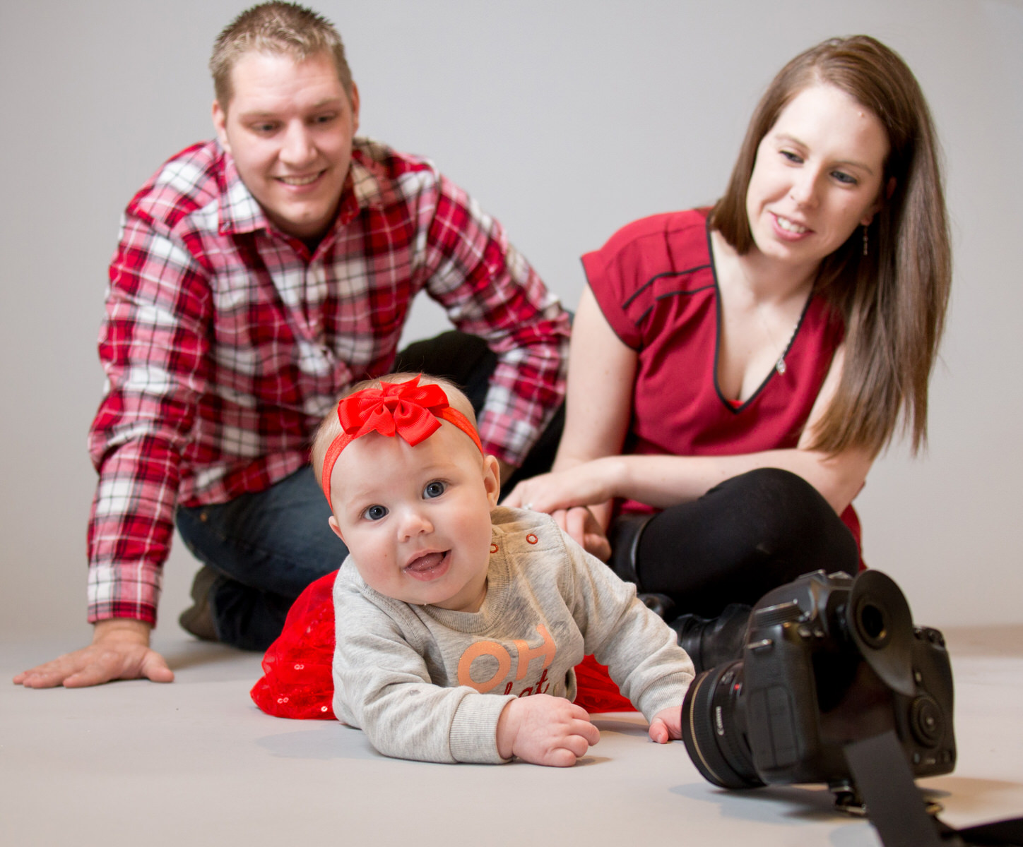 Baby crawls on tummy to reach for camera during family portraits in Erie, PA