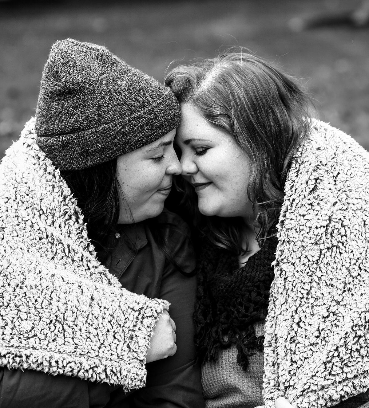 Couple snuggles under a blanket for portraits in Erie PA