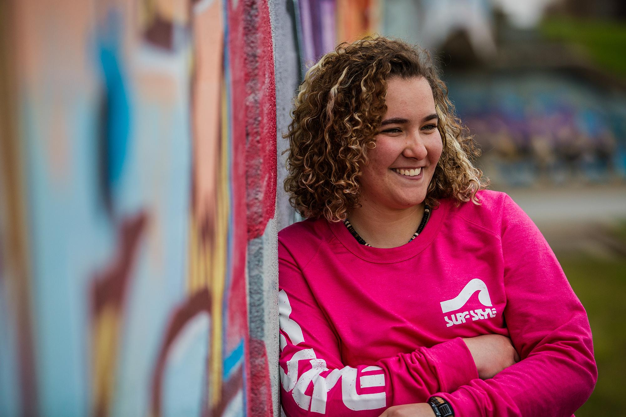 Girl stands next to graffiti walk during Erie senior portraits