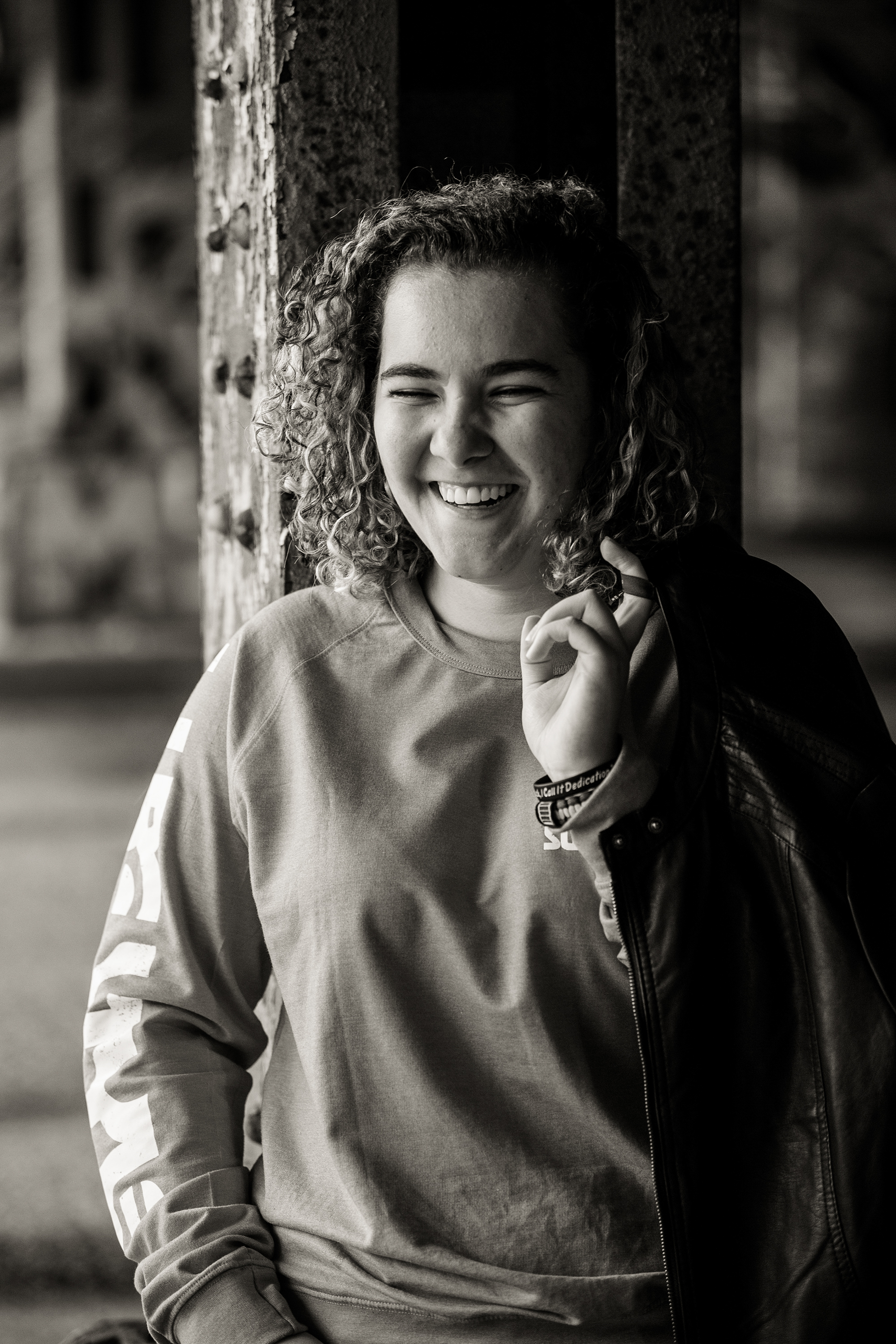 Erie senior portraits of laughing girl holding leather jacket under 14th St. underpass