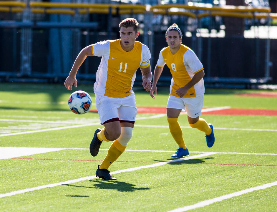 Gannon University men's soccer players running after soccer ball
