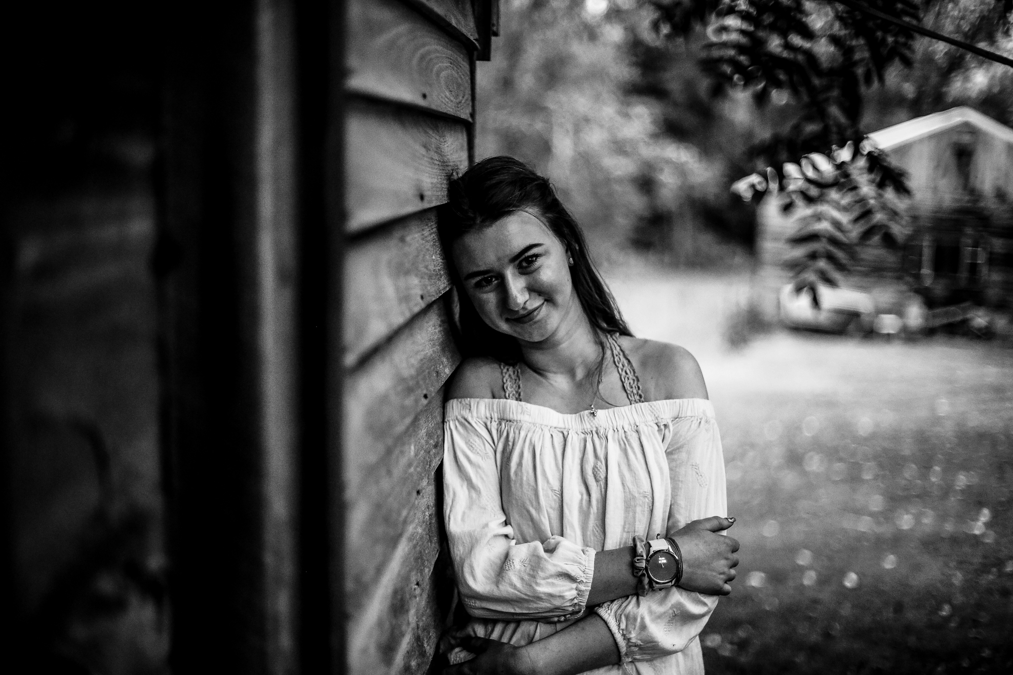 Girl leans against farmhouse house in rustic senior portraits