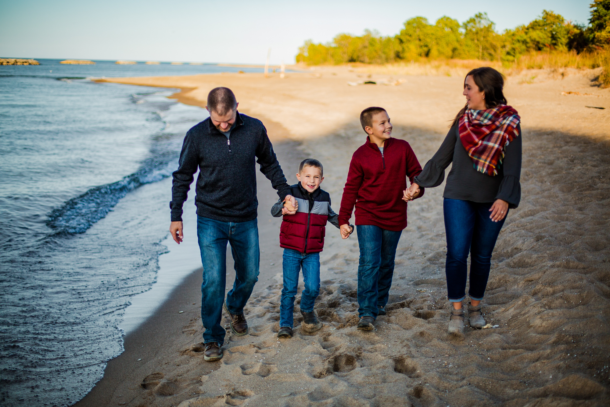 Family walks on the beach at Presque Isle State Park during portrait session