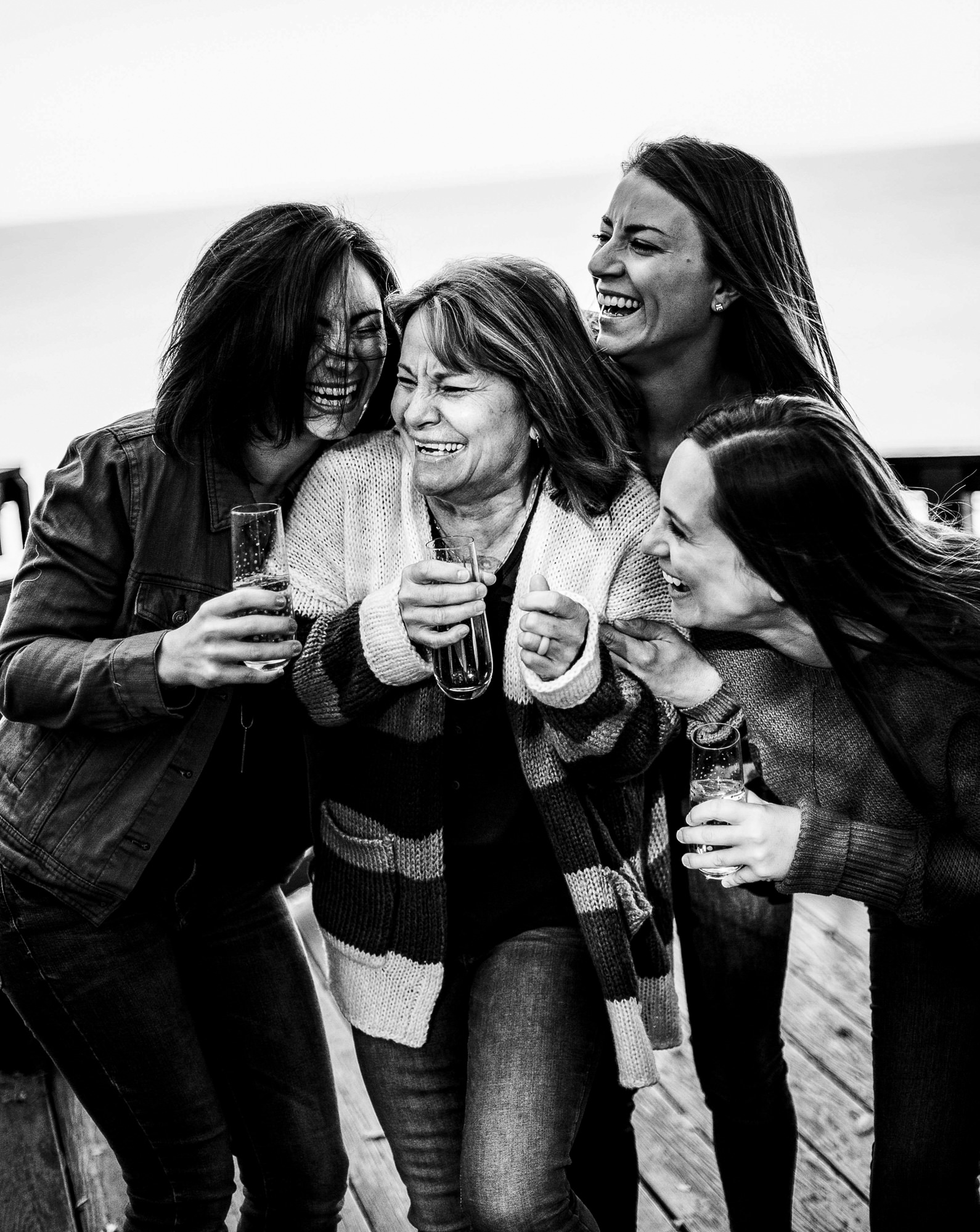 Mother and three daughters laugh over glasses of champagne for family portraits in Erie, PA